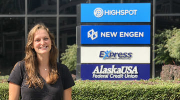 Kirstin Johnson (MMark'18) in front of New Engen Logo