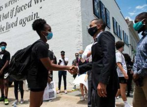 Organizer Grace Jackson shakes hands with Reed