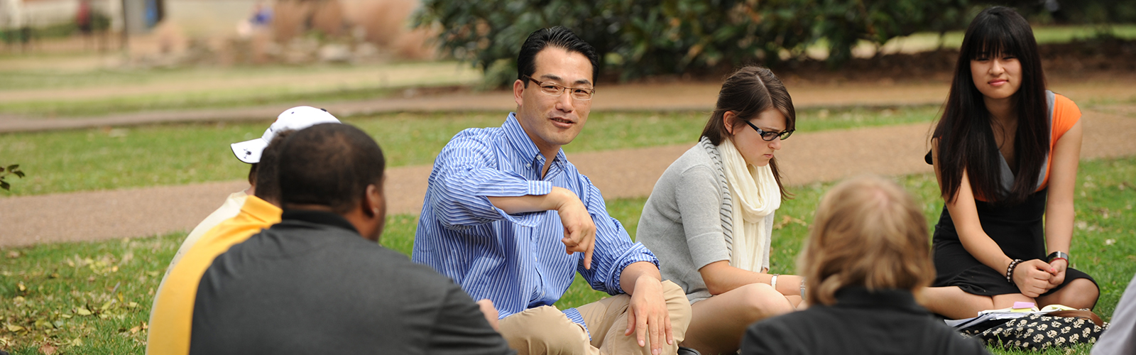 Jeong-Oh Kim teaches Intro to Poetry sitting with students on Library Lawn