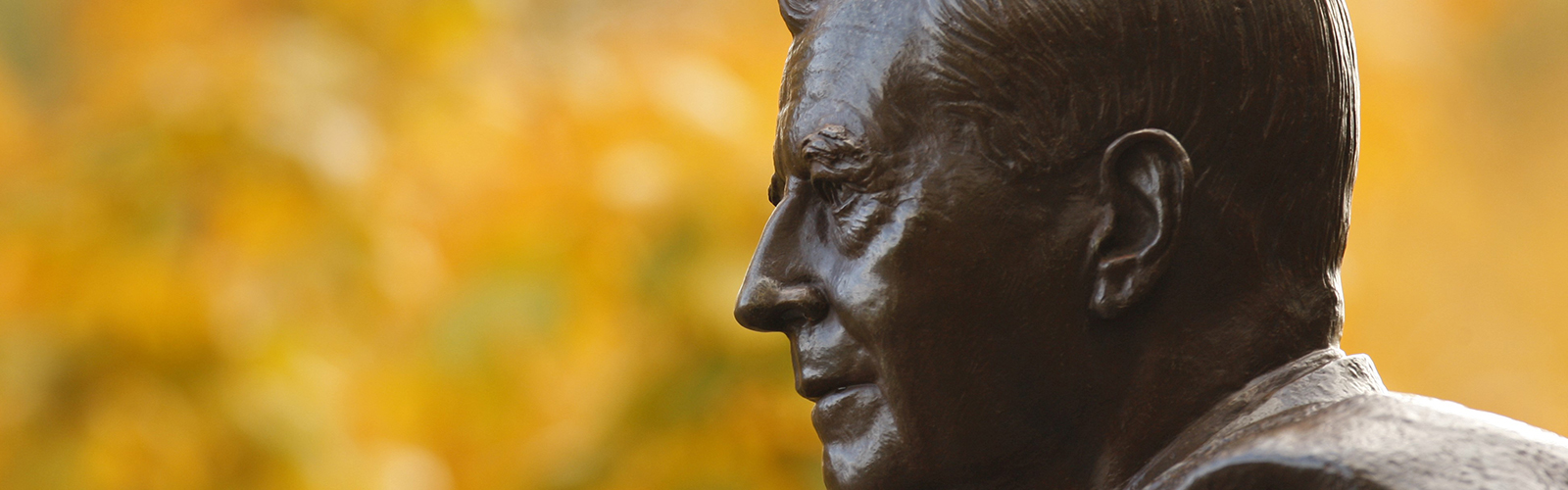 closeup of a statue of Harold Stirling Vanderbilt with trees in the background, located on the Vanderbilt campus