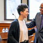 Houston Baker laughs with a student at an event in a meeting room