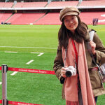 Yining Ding standing in Liverpool soccer stadium with the field and empty stands behind her