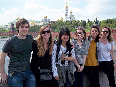 Six students leaning against a wall in a Russian city with a river and gold-domed towers and buildings in the background