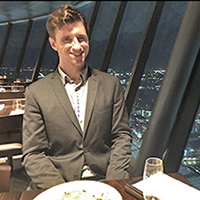 Devon Akers sitting at a table in a restaurant with a window and night view of a city in the background