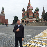 Mark Pettus holding a cup of coffee and standing on pavement in Moscow with a clock tower and colorfully painted, domed building behind him