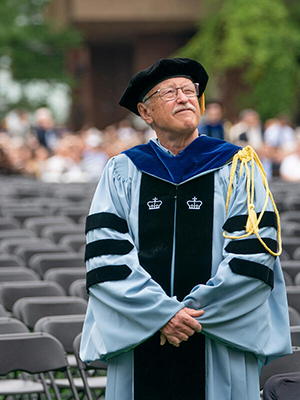 Frank Wcislo in academic regalia standing in front of empty rows of seats at Vanderbilt Commencement