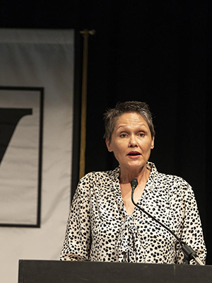 Joy Calico standing at a lectern and speaking with a Vanderbilt flag behind her