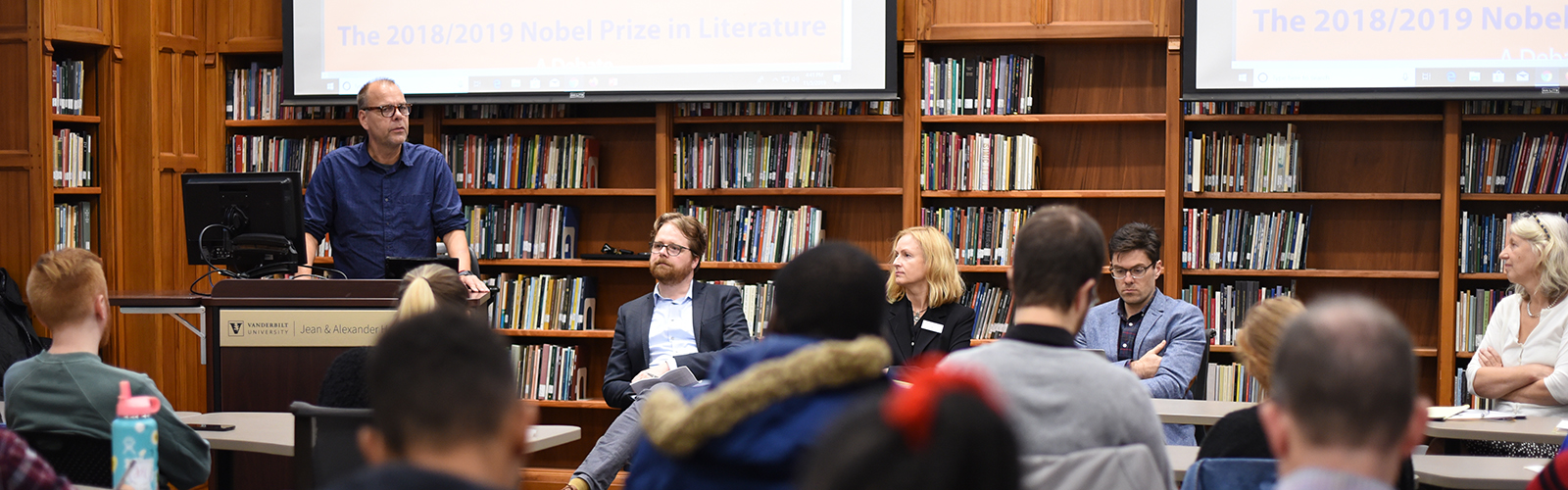 one faculty member stands at a lectern and four others sit at a long table in front of a book-lined room of seated students and faculty