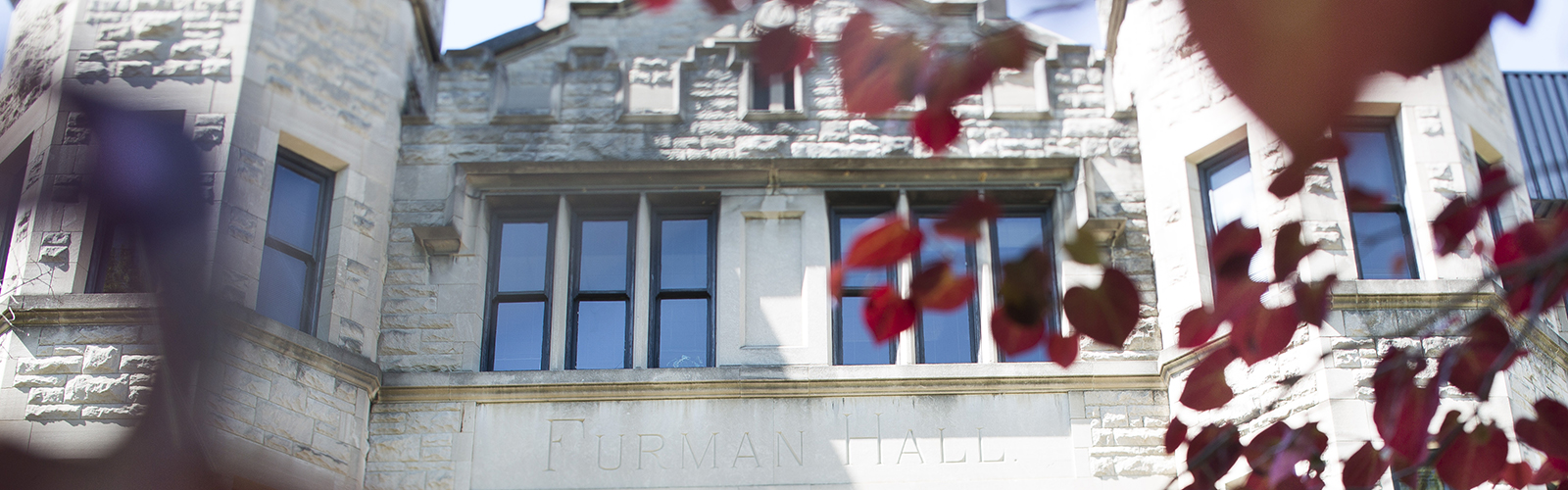 exterior of Furman Hall, a light gray stone building, with red leaves in the foreround