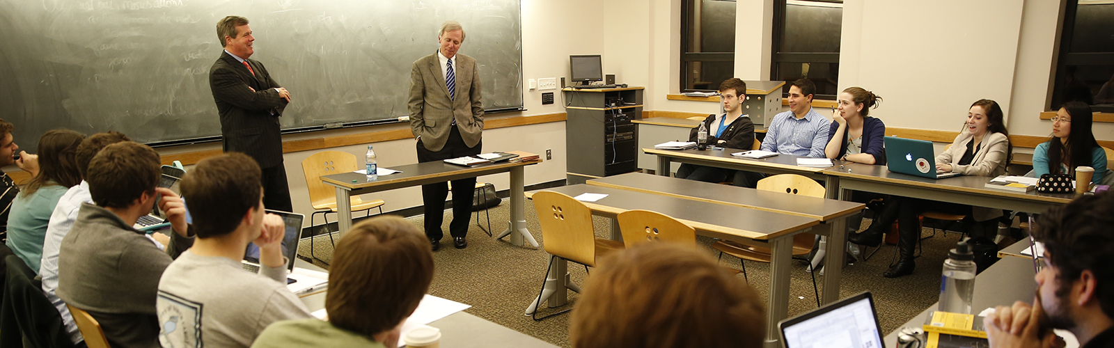 Professor Bill Purcell and former Nashville mayor Karl Dean speak to students sitting around tables in a public policy studies class