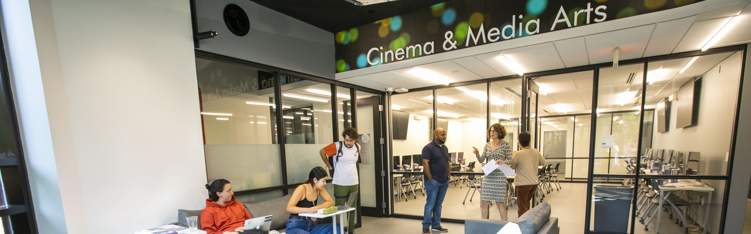 Lobby of Cinema and Media Arts department; students sitting in colorful chairs working on laptops; faculty standing and talking in front of glass wall
