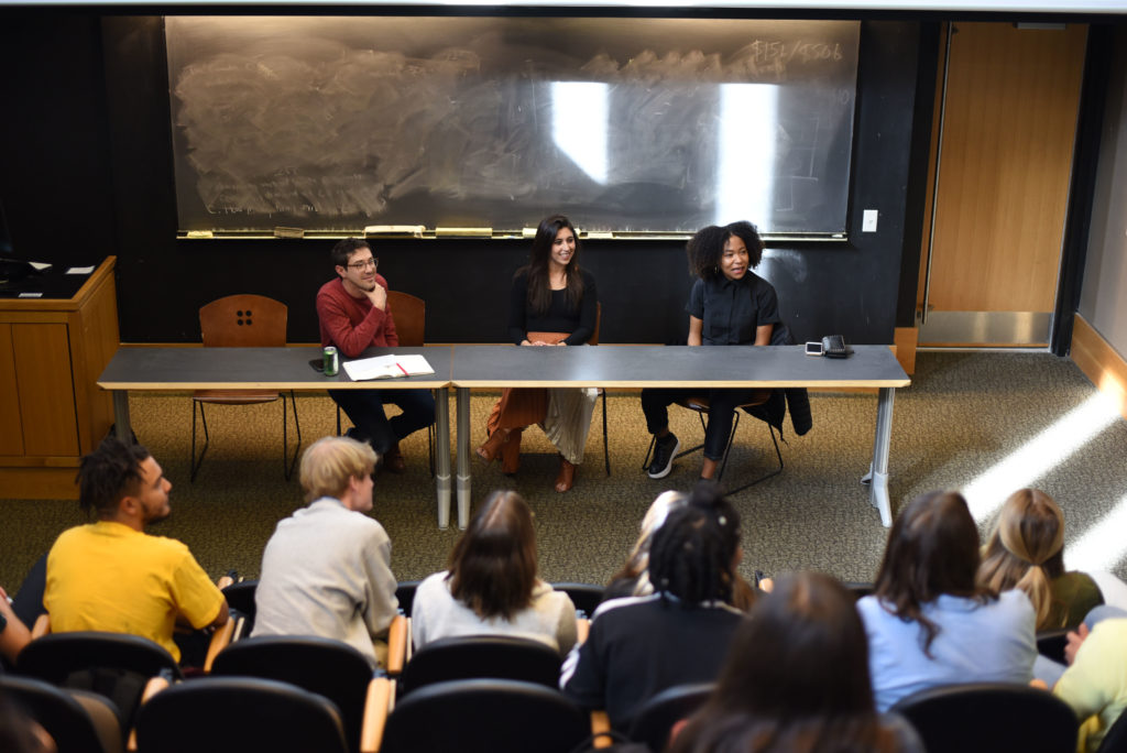 Prof Rattner and two alumni guest speakers sit and talk to a crowd in a lecture hall