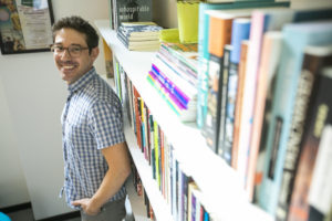 A headshot of Jonathan Rattner, a white man with dark hair and stubble wearing glasses and a plaid button down standing against a bookshelf and looking over his shoulder at the camera
