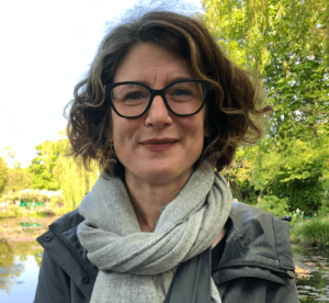 A headshot of Jennifer Fay, a white woman with curly brown hair wearing glasses and a grey scarf with trees and water in the background