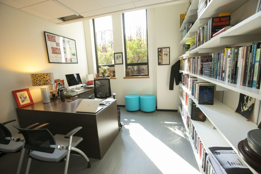 Prof Fay's office which has large windows, a wall of book shelves, a brown L shaped desk, and several framed art pieces