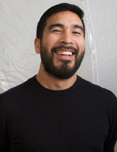 A headshot of Alejandro Acierto, a brown-skinned man with dark hair and beard who is laughing and wearing a black shirt
