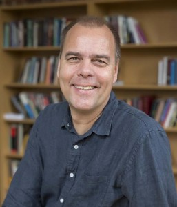 A headshot of Lutz Koepnick, a white man with close cropped hair wearing a navy button down shirt with bookshelves in the background