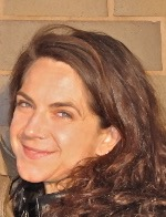 A headshot of Mickey Casad, a white woman with brown hair looking over her shoulder at the camera