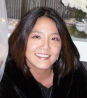 A headshot of Helen Shin, an Asian woman with dark hair wearing a black shirt