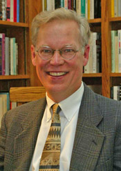 A headshot of Jay Clayton, a white man with white hair and glasses wearing a gray suit jacket and a patterned brown tie with books in the background