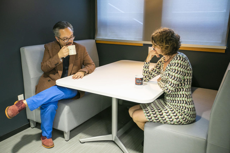 Two faculty members talking and having coffee at a table in the department lounge area