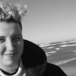 A head shot of Bo Broder, a nonbinary person with bleached hair and a black jacket standing on the beach