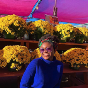 Mariam Sanusi standing in front of buckets of yellow flowers