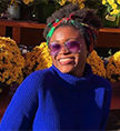 Photo of Mariam Sanusi in front of buckets of yellow flowers