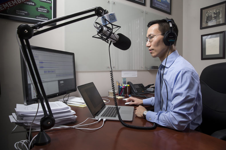 photo of Ed Cheng at a microphone