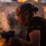 """Woman lighting copal incense at the cemetery during the """"Alumbrada"""" vigil in San Andrés Mixquic"""