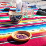 Glitter Ashes in a small terra cotta dish. They are on a woven blanket of rainbow colors in the sun. There are candles and other bowls in the background.
