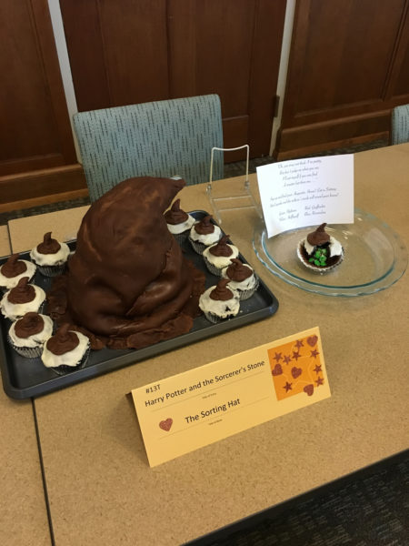 A cake shaped like the Sorting Hat, surrounded by cupcakes with mini-sorting hats on top.