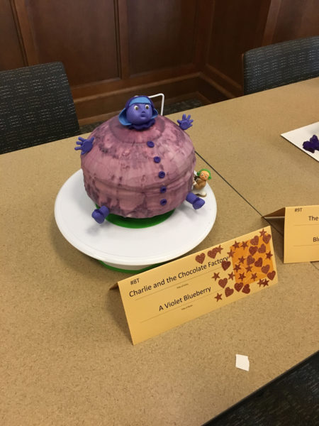 A cake made to look like Violet Beauregarde as a blueberry.