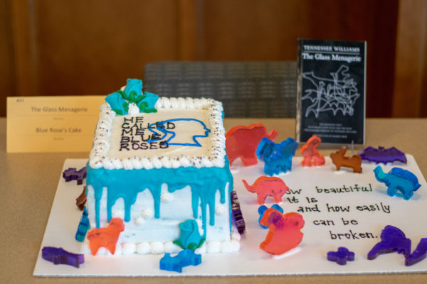 """A white cake with blue icing and the quote """"He called me blue roses"""" written in icing."""