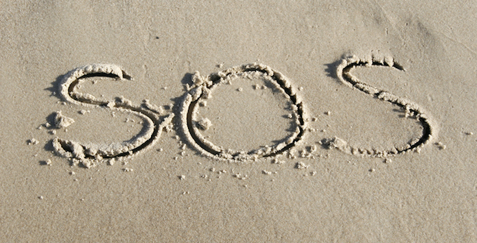 SOS written in sand on beach