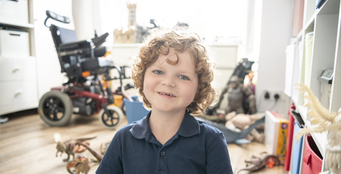 Cheerful boy sitting on playroom floor, looking towards the camera, smiling, with electric wheelchair in the background