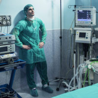 worried or sad looking surgeon leaning against wall of empty operating theater in scrubs