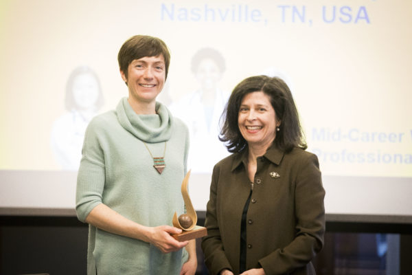 Jessica Dennis, postdoctoral fellow in the Division of Genetic Medicine and research fellow in the Cox Lab accepts the Mary Jane Werthan Award from Women's Center Director Rory Dicker on behalf of Nancy Cox, Director of the Vanderbilt Genetics Institute and Mary Phillips Edmonds Gray Professor of Genetics. (Susan Urmy/Vanderbilt)