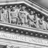 "Close-up in black and white of the message ""Equal Justice Under Law"" inscribed in the classically detailed US Supreme Court building in Washington, DC, USA"