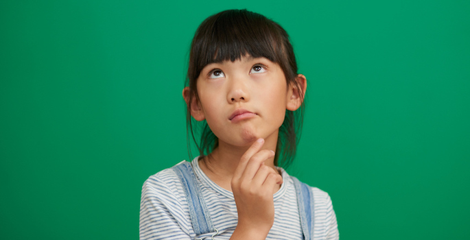 Asian girl looking thoughtful with hand in chin against a green background