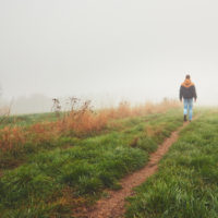 Lonely young white man walking on a path through a field on a foggy day