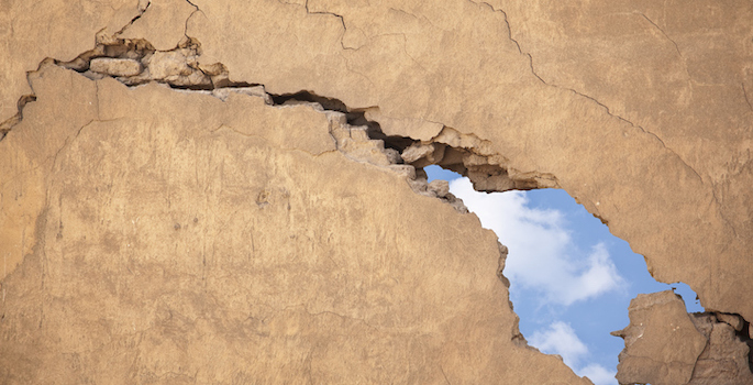 concrete wall with large crack and hole in it, revealing sky behind it