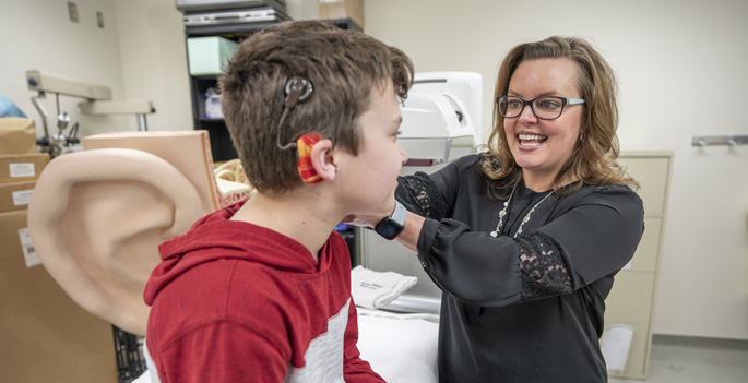 doctor adjusting child's cochlear implant with her hand