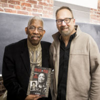 '60s Freedom Rider Rip Patton holds 'Breach of Peace' book in which Patton's mugshot is included. Standing next to him is author Eric Etheridge