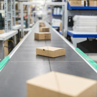 Cardboard boxes on moving belt conveyor at distribution warehouse. Modern warehouse with automatic moving conveyor machine.