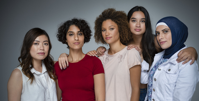 Portrait of a Group of women in the studio. Multi-ethnic group including Caucasian, Hispanic, middle eastern, Asian and African American. One middle eastern woman is wearing a hijab (Portrait of a Group of women in the studio. Multi-ethnic group inclu