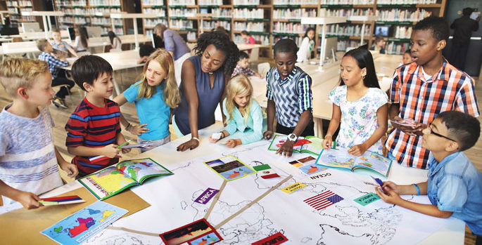 African American woman teacher working with diverse students in a school library