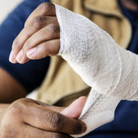 african american man wrapping gauze around his hand