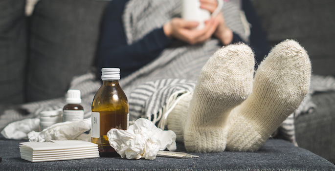 person wearing socks and wrapped in a blanket curled up on sofa with cold medicine