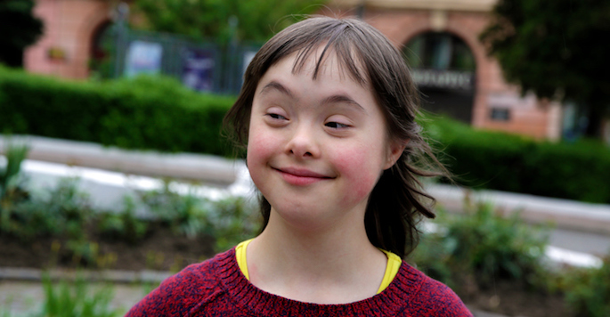 smiling caucasion girl who has down syndrome